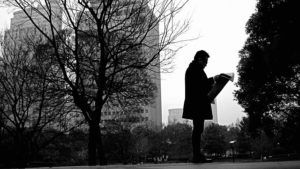 reading newspaper in park